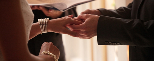 wedding groom putting ring on bride's finger